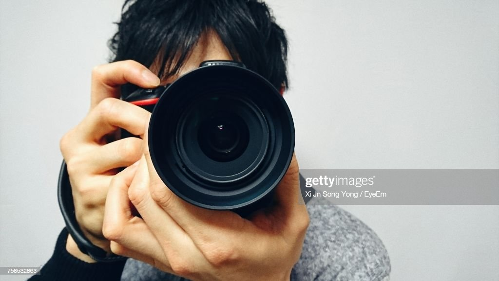 Close-Up Of Man Photographing Against Gray Background : Foto de stock