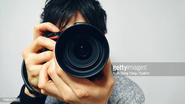 Close-Up Of Man Photographing Against Gray Background