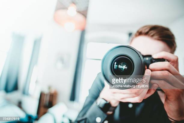 Close-Up Of Man Photographing At Home