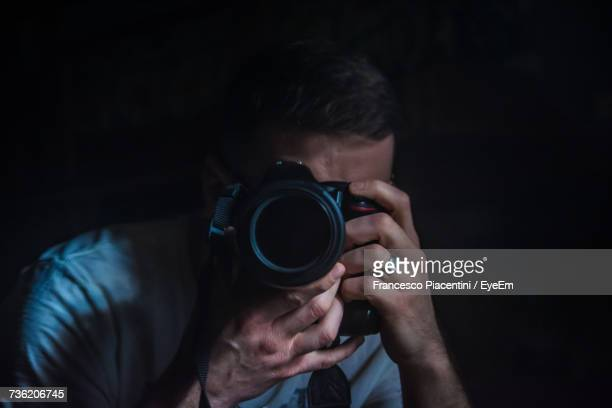 Close-Up Of Man Photographing Through Dslr Against Black Background