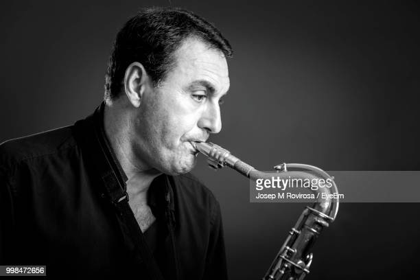 Close-Up Of Man Playing Brass Instrument Against Gray Background