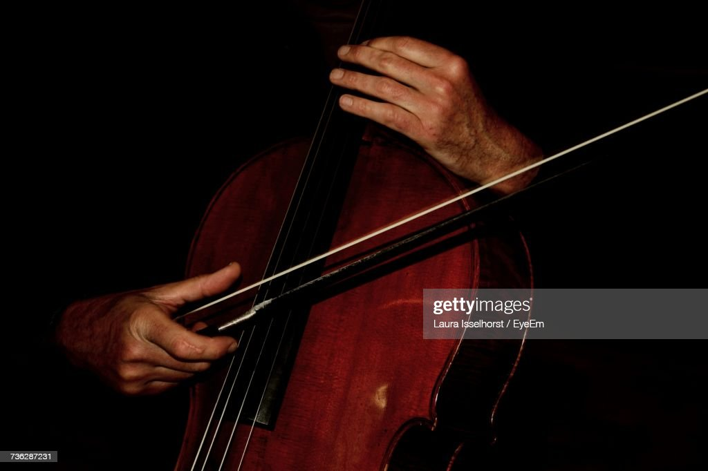 Close-Up Of Man Playing Cello Against Black Background : Stock Photo