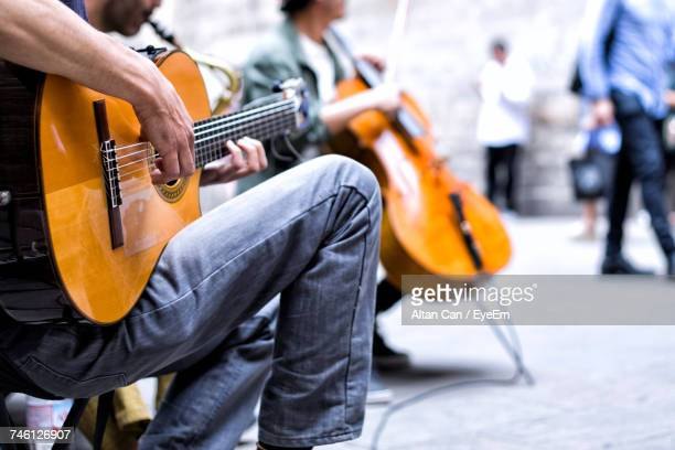 close-up of man playing guitar - street artist stock pictures, royalty-free photos & images