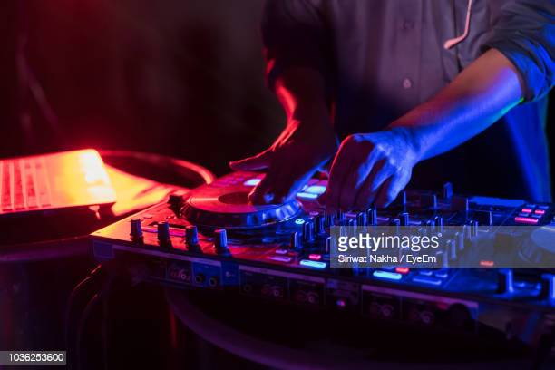 close-up of man playing music on audio equipment in nightclub - club dj stock pictures, royalty-free photos & images
