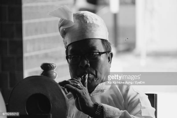 close-up of man playing musical instrument while sitting outdoors - ko ko htike aung stock pictures, royalty-free photos & images