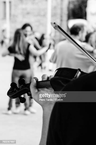 Close-Up Of Man Playing Violin With Couple Dancing In Background