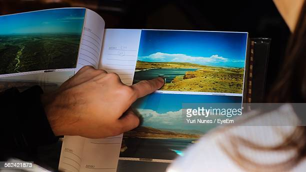 Close-Up Of Man Pointing At Photo In Album