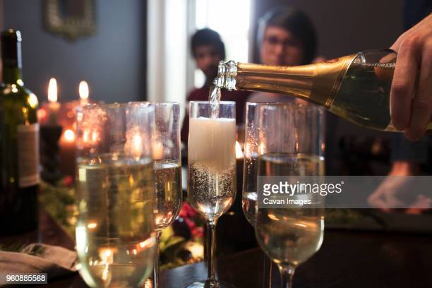 Close-up of man pouring champagne in glasses during Christmas party