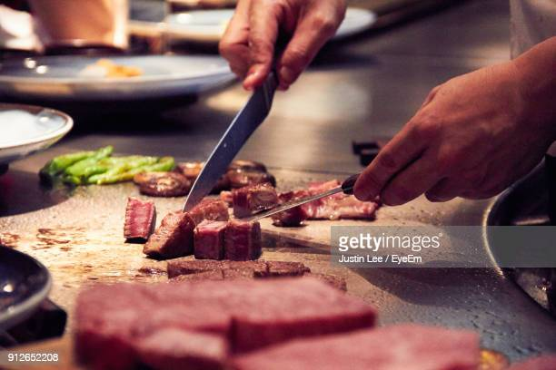 Close-Up Of Man Preparing Food On Cutting Board