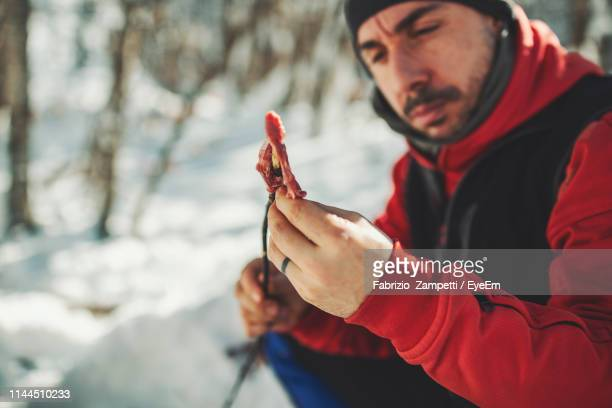 close-up of man preparing meat during winter - fabrizio zampetti foto e immagini stock
