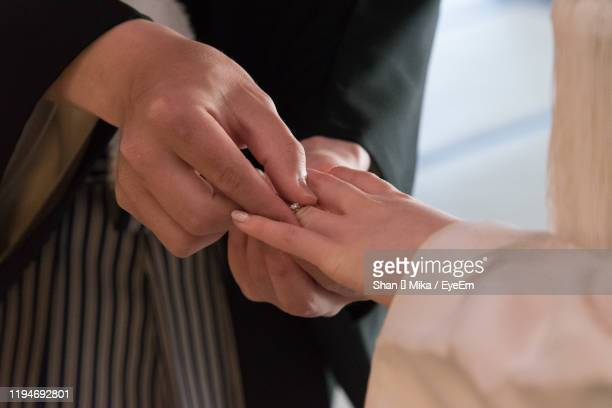 close-up of man putting ring in woman finger - 結婚指輪 ストックフォトと画像