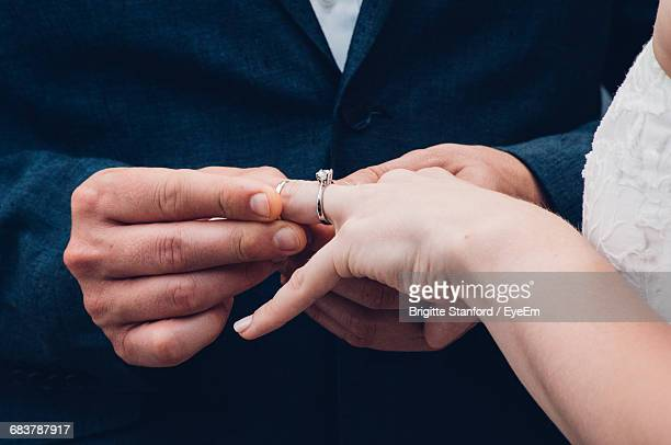 Close-Up Of Man Putting Ring On Brides Hand