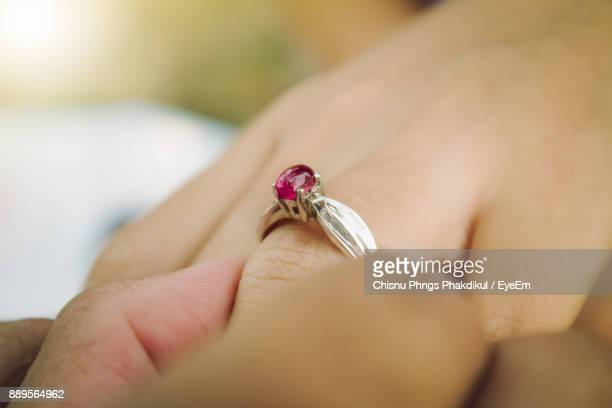 Close-Up Of Man Putting Ring On Woman Hand