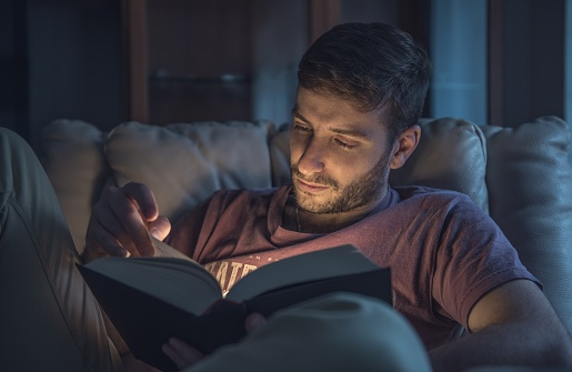 Close-Up Of Man Reading Book While Sitting On Sofa At Home - gettyimageskorea
