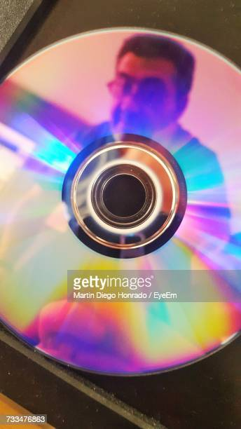 Close-Up Of Man Reflecting On Compact Disc