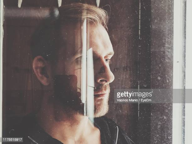 close-up of man reflecting on mirror - one mid adult man only stock pictures, royalty-free photos & images