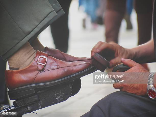 Close-Up Of Man Shining Shoes Outdoors