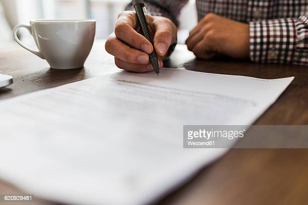 close-up of man signing document on table - human body part stock pictures, royalty-free photos & images