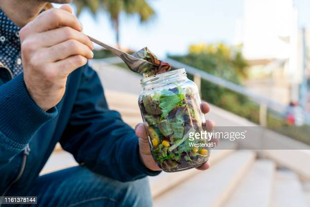 close-up of man sitting on stairs having lunch break - jars with salad stock pictures, royalty-free photos & images