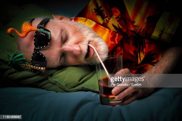 Close-Up Of Man Sleeping While Drinking Alcohol