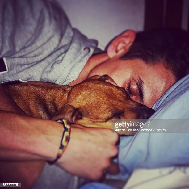 close-up of man sleeping with dog on bed at home - gonzalo caballero fotografías e imágenes de stock