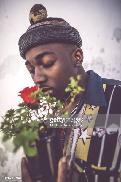 Close-Up Of Man Smelling Red Flowering Plants