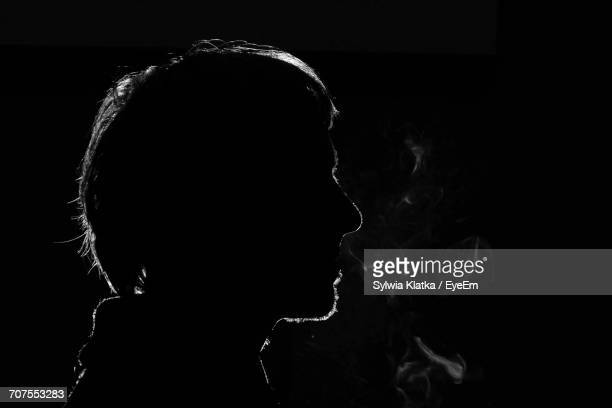close-up of man smoking against black background - comportement addictif photos et images de collection