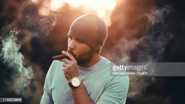close-up of man smoking cigar standing outdoors - cigar stock pictures, royalty-free photos & images