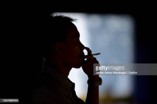close-up of man smoking cigarette at night - arthur stock pictures, royalty-free photos & images