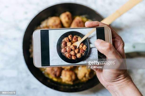 close-up of man taking a picture of meatballs with smart phone - croquette stock photos and pictures