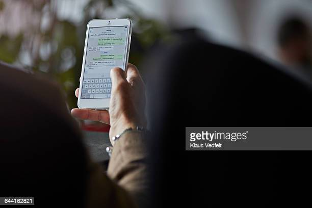 close-up of man texting with girl friend on phone - sms'en stockfoto's en -beelden