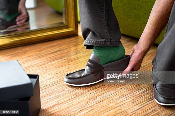 close-up of man trying on new moccasins shoes, wardrobe interior - menselijk lichaamsdeel stockfoto's en -beelden