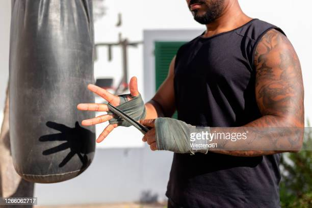 close-up of man tying bandage on hand while standing by punching bag in yard - martial arts stock pictures, royalty-free photos & images