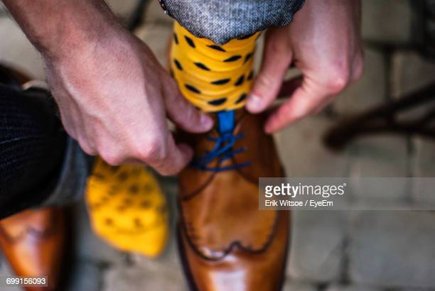 close-up of man tying shoelaces - yellow shoe stock photos and pictures