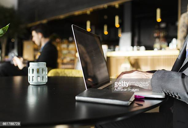 Close-up of man typing on laptop while sitting at restaurant