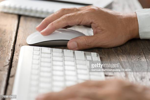 Close-Up Of Man Using Computer On Table