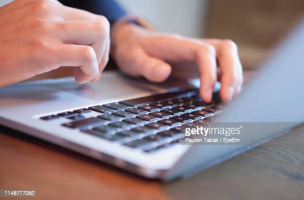close-up of man using laptop at desk - paulien tabak stock pictures, royalty-free photos & images