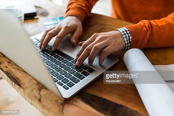close-up of man using laptop next to construction plan at desk - typen stockfoto's en -beelden