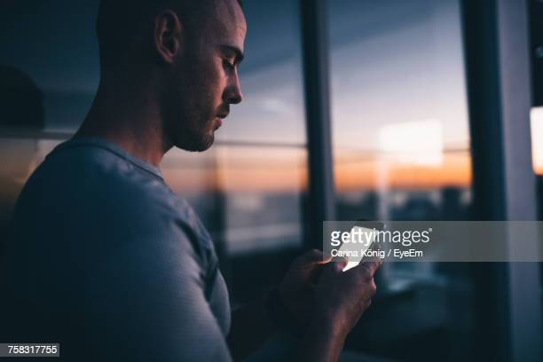 close-up of man using mobile phone at sunset - portability stock pictures, royalty-free photos & images