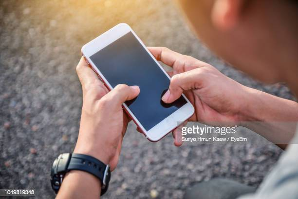 close-up of man using mobile phone outdoors - iphone screen stock pictures, royalty-free photos & images