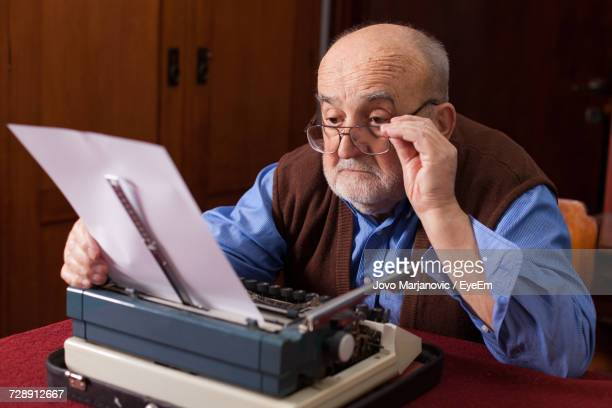 close-up of man using typewriter - authors stock pictures, royalty-free photos & images