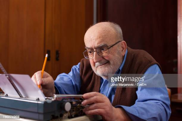 close-up of man using typewriter - authors stock photos and pictures