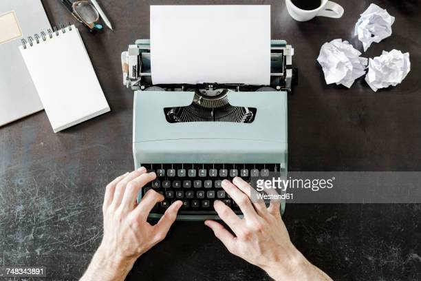 close-up of man using typewriter with crumpled paper on desk - authors stockfoto's en -beelden