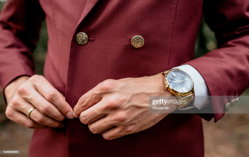 Close-up of man wearing a suit and golden watch buttoning his jacket : Stock Photo