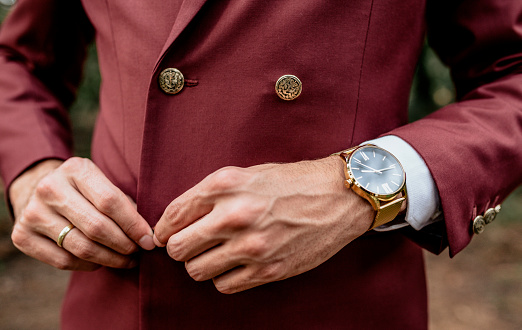 Close-up of man wearing a suit and golden watch buttoning his jacket - gettyimageskorea