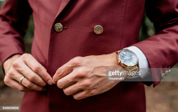 close-up of man wearing a suit and golden watch buttoning his jacket - elegancia fotografías e imágenes de stock