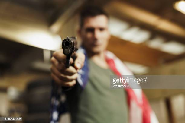 close-up of man wearing american flag aiming with a gun - mord stock-fotos und bilder
