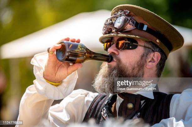 close-up of man wearing costume while having drink during carnival - steve guessoum stockfoto's en -beelden