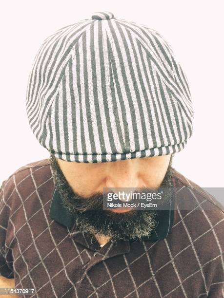 close-up of man wearing flat cap against white background - flat cap stock pictures, royalty-free photos & images