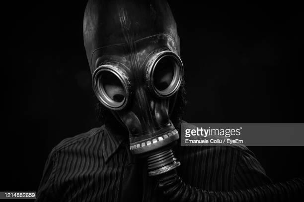 close-up of man wearing gas mask against black background - black mask disguise stock pictures, royalty-free photos & images
